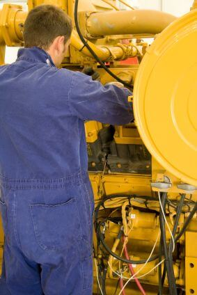 A technician performing periodic engine maintenance in a landfill gas recovery plant